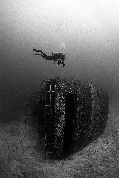diver diving over wreck black and white photography